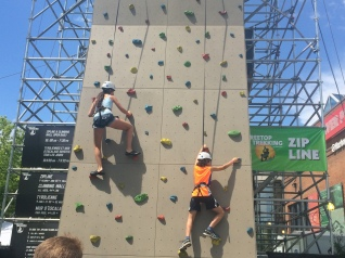 Camper testing out the ropes at the rock climbing wall!