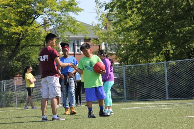 FOY staff coaching a camper in soft ball.