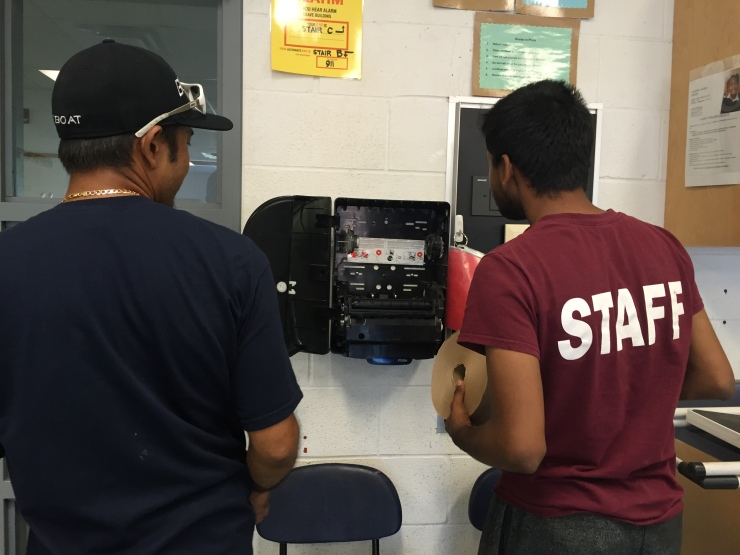 West teaching Prasath how to put on new paper towels in the dispenser.