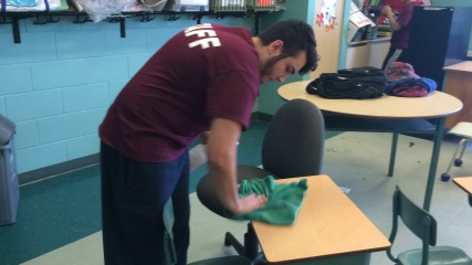 Cleaning desks and chairs is one of his many duties throughout the day