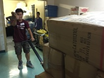 Kevin giving a thumbs up while moving heavy boxes