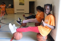 Campers relaxing on basketballs