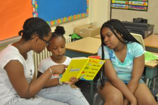 Campers helping their other campers read.