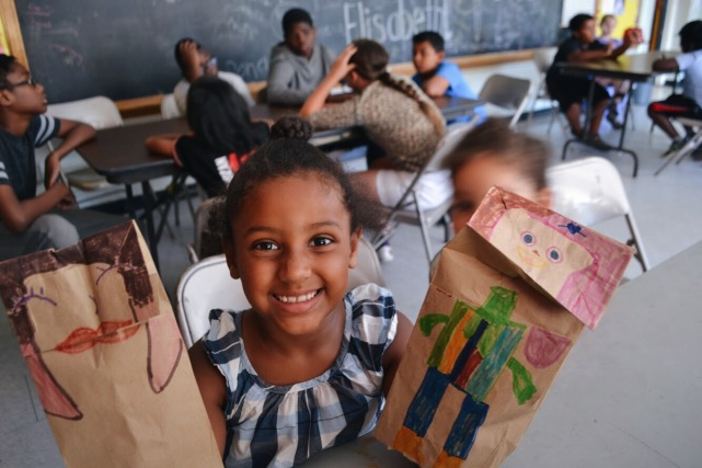 Camper showing off her paper bag puppets.