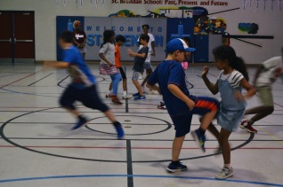 Playing a game of Huckle Buckle with the other campers in the gym.