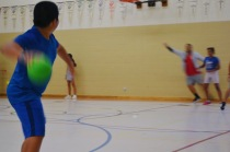 Campers and staff playing a game of King's Court dodgeball in the gym.
