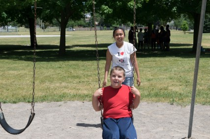 Camper and camp counselor having fun on the swings!